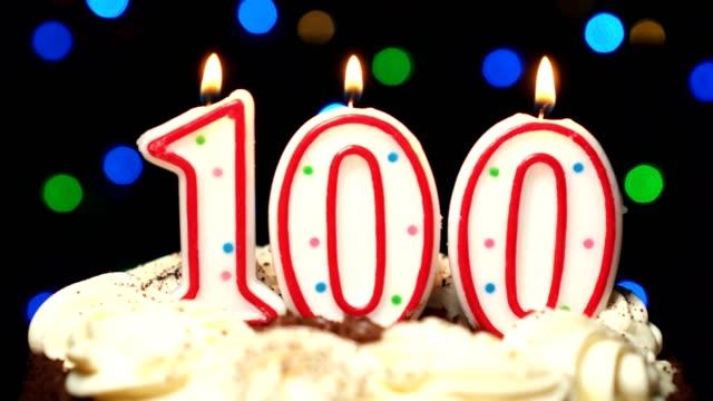 Numéro 100 sur gâteau - anniversaire de cent bougies brûlant - souffler à la fin. Couleur d'arrière-plan flou - Vidéo