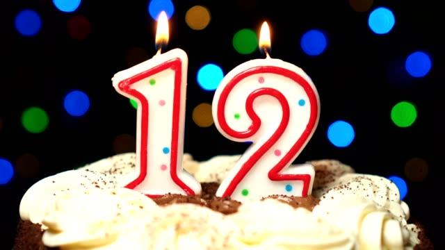 Numéro 12 sur gâteau - anniversaire douze bougie brûle - souffler à la fin. Couleur d'arrière-plan flou - Vidéo