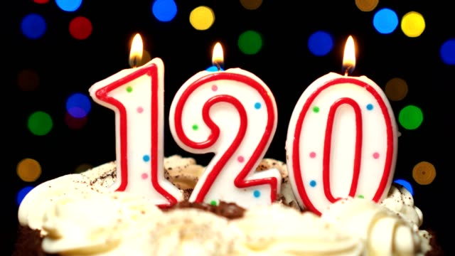Numéro 120 sur gâteau - anniversaire de cent vingt bougies brûlant - souffler à la fin. Couleur d'arrière-plan flou - Vidéo