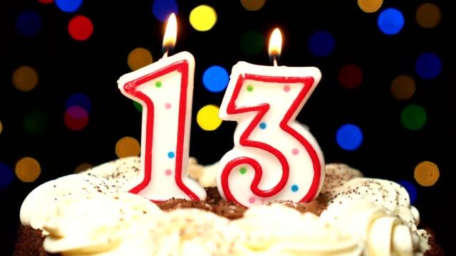 N ° 13 sur gâteau - anniversaire treize bougie brûle - souffler à la fin. Couleur d'arrière-plan flou - Vidéo