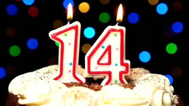 Le numéro 14 sur gâteau - anniversaire quatorze bougie brûle - souffler à la fin. Couleur d'arrière-plan flou - Vidéo