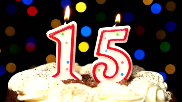 Number 15 on top of cake - fifteen birthday candle burning - blow out at the end. Color blurred background video