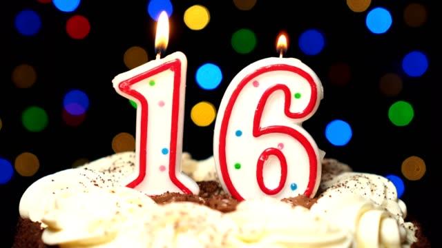 Numéro 16 sur gâteau - anniversaire seize bougie brûle - souffler à la fin. Couleur d'arrière-plan flou - Vidéo
