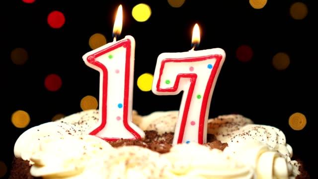 Numéro 17 sur gâteau - anniversaire dix-sept bougie brûle - souffler à la fin. Couleur d'arrière-plan flou - Vidéo
