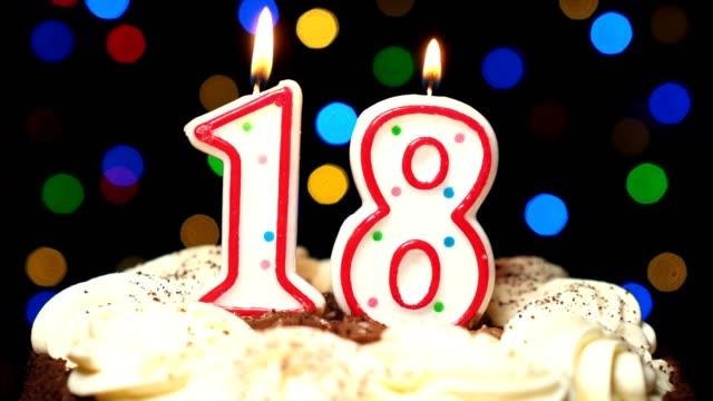 Le numéro 18 sur gâteau - anniversaire dix-huit bougie brûle - souffler à la fin. Couleur d'arrière-plan flou - Vidéo