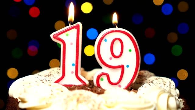 Le numéro 19 sur gâteau - anniversaire dix-neuf bougie brûle - souffler à la fin. Couleur d'arrière-plan flou - Vidéo