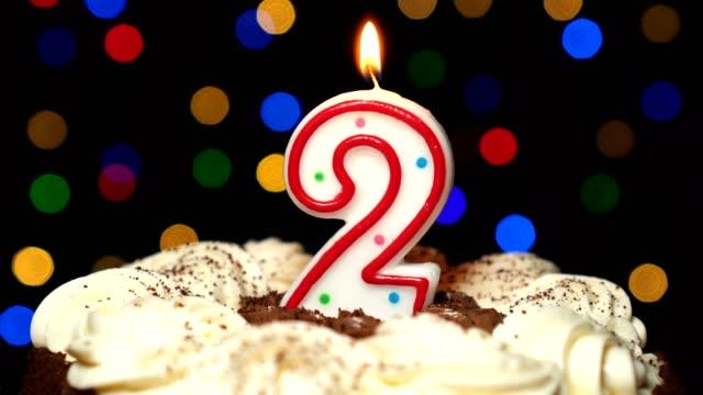 Numéro 2 sur le dessus de gâteau - anniversaire deux bougie brûle - souffler à la fin. Couleur d'arrière-plan flou - Vidéo