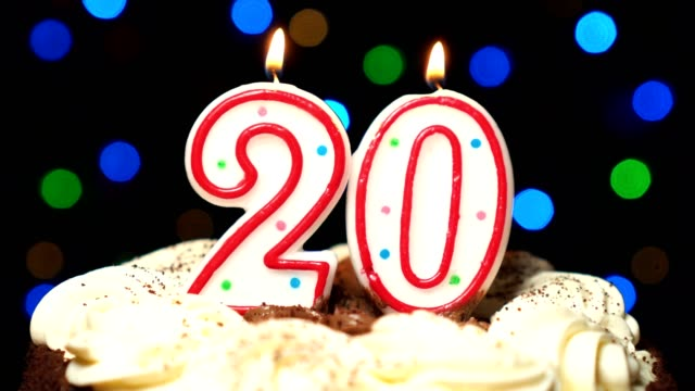 Number 20 on top of cake - twenty birthday candle burning - blow out at the end. Color blurred background video