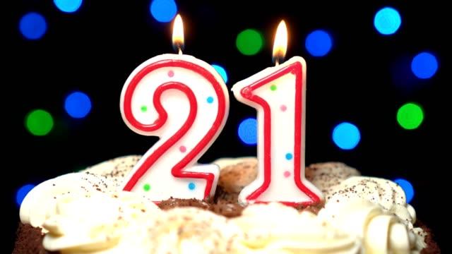 Numéro 21 sur gâteau - vingt et un, anniversaire bougie brûle - souffler à la fin. Couleur d'arrière-plan flou - Vidéo