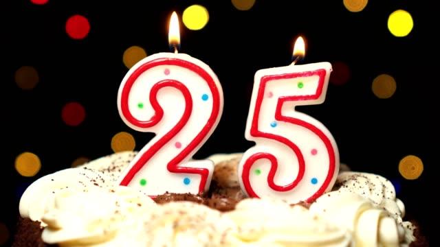 Numéro 25 sur le dessus de coup de gâteau - anniversaire de vingt-cinq bougies burning - out à la fin. Couleur d'arrière-plan flou - Vidéo