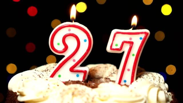 Numéro 27 sur le dessus de coup de gâteau - anniversaire de vingt-sept bougie brûle - out à la fin. Couleur d'arrière-plan flou - Vidéo
