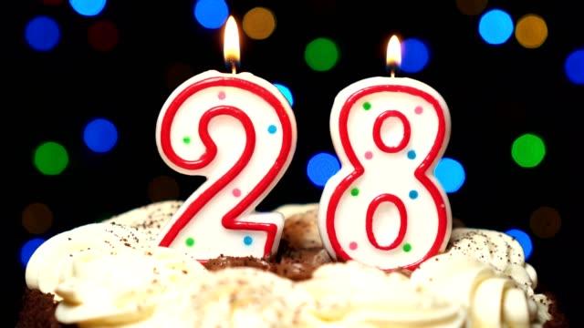 Numéro 28 sur le dessus de coup de gâteau - anniversaire de vingt-huit bougie brûle - out à la fin. Couleur d'arrière-plan flou - Vidéo