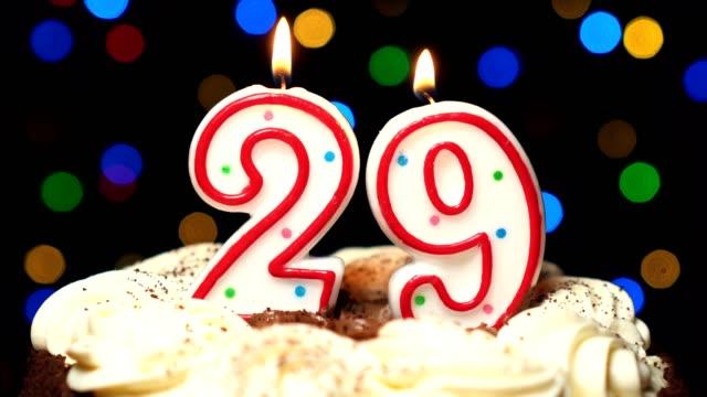 Numéro 29 sur le dessus de coup de gâteau - anniversaire de vingt-huit bougie burning - out à la fin. Couleur d'arrière-plan flou - Vidéo