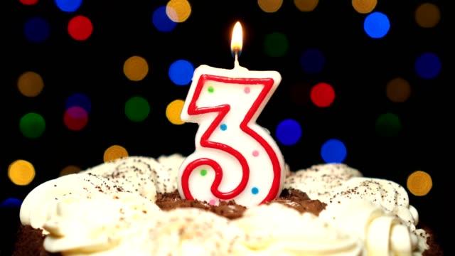 Numéro 3 sur le dessus de gâteau - anniversaire de trois bougie brûle - souffler à la fin. Couleur d'arrière-plan flou - Vidéo