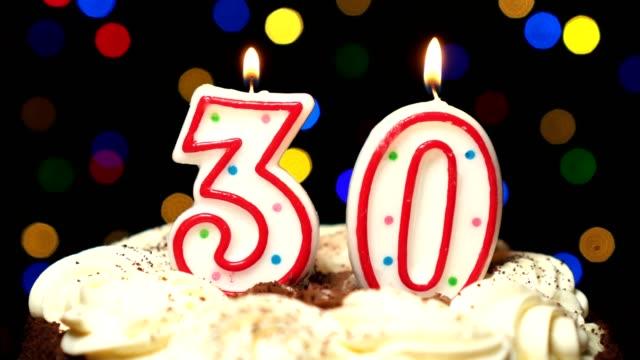 Numéro 30 sur gâteau - anniversaire trente bougie brûle - souffler à la fin. Couleur d'arrière-plan flou - Vidéo