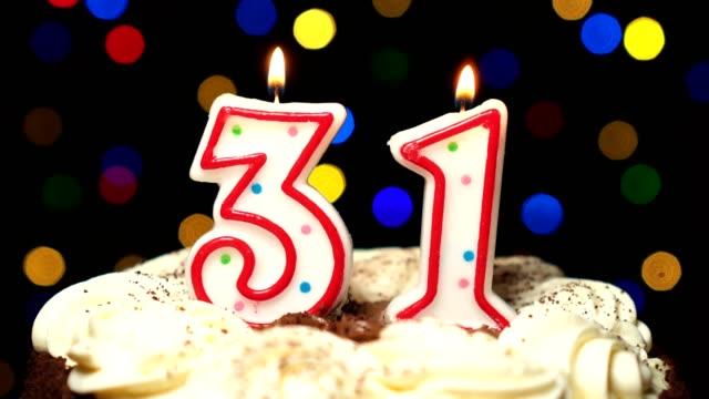 Numéro 31 sur gâteau - anniversaire de trente une bougie brûle - souffler à la fin. Couleur d'arrière-plan flou - Vidéo