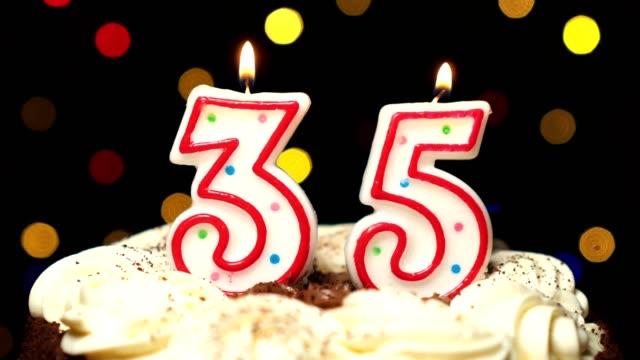 Numéro 35 sur gâteau - anniversaire de trente-cinq bougie brûle - souffler à la fin. Couleur d'arrière-plan flou - Vidéo
