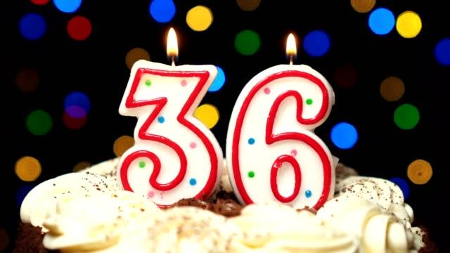 Numéro 36 sur gâteau - anniversaire de trente-six bougie brûle - souffler à la fin. Couleur d'arrière-plan flou - Vidéo