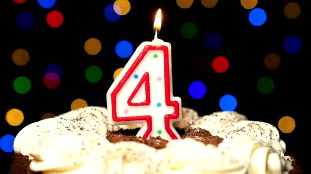 stockvideo's en b-roll-footage met nummer 4 op de top van taart - vier verjaardag kaars branden - klap uit aan het einde. onscherpe achtergrond kleur - vier personen