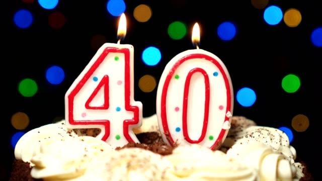 Numéro 40 sur gâteau - anniversaire quarante bougies brûlant - souffler à la fin. Couleur d'arrière-plan flou - Vidéo