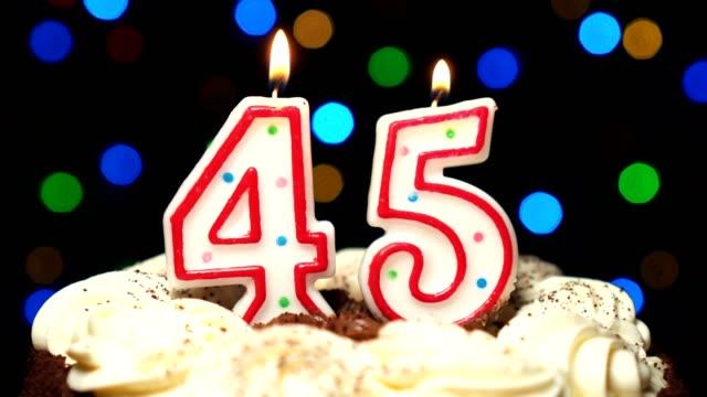 Numéro 45 sur gâteau - anniversaire de quarante-cinq bougies brûlant - souffler à la fin. Couleur d'arrière-plan flou - Vidéo