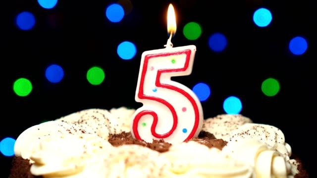 Numéro 5 sur gâteau - anniversaire cinq bougie brûle - souffler à la fin. Couleur d'arrière-plan flou - Vidéo