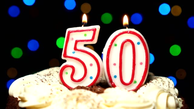 Number 50 on top of cake - fifty birthday candle burning - blow out at the end. Color blurred background video