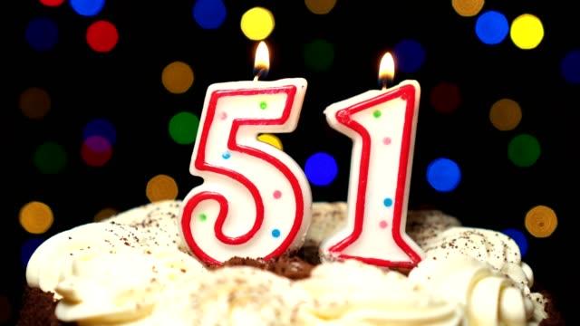 Numéro 51 sur gâteau - anniversaire de cinquante une bougie brûle - souffler à la fin. Couleur d'arrière-plan flou - Vidéo