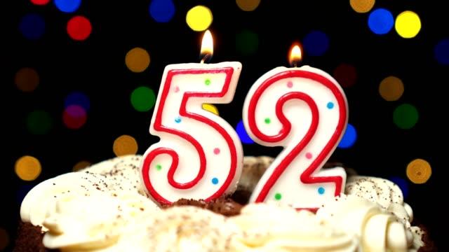 Numéro 52 sur gâteau - anniversaire de cinquante deux bougie brûle - souffler à la fin. Couleur d'arrière-plan flou - Vidéo