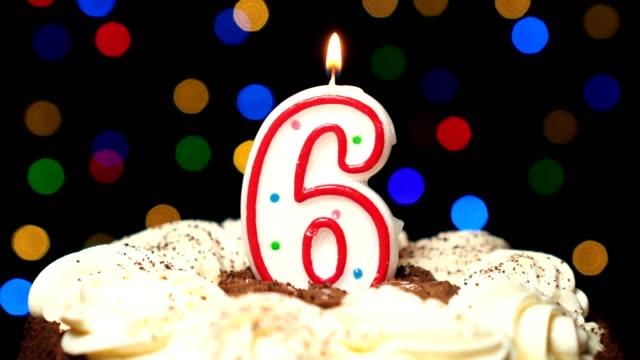 Numéro 6 sur gâteau - anniversaire six bougies brûlant - souffler à la fin. Couleur d'arrière-plan flou - Vidéo