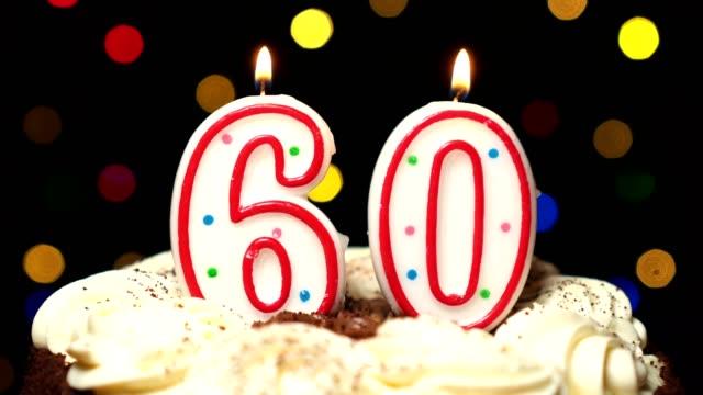 Numéro 60 sur gâteau - anniversaire soixante bougies brûlant - souffler à la fin. Couleur d'arrière-plan flou - Vidéo