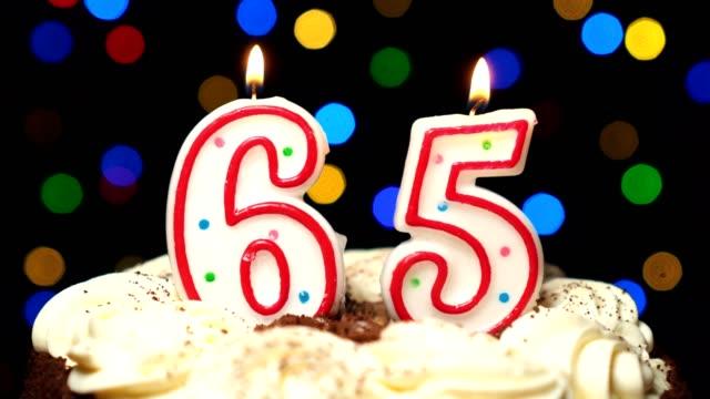 Numéro 65 sur gâteau - anniversaire de soixante-cinq bougie brûle - souffler à la fin. Couleur d'arrière-plan flou - Vidéo