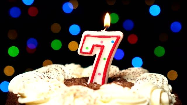 Numéro 7 sur gâteau - anniversaire sept bougies brûlant - souffler à la fin. Couleur d'arrière-plan flou - Vidéo