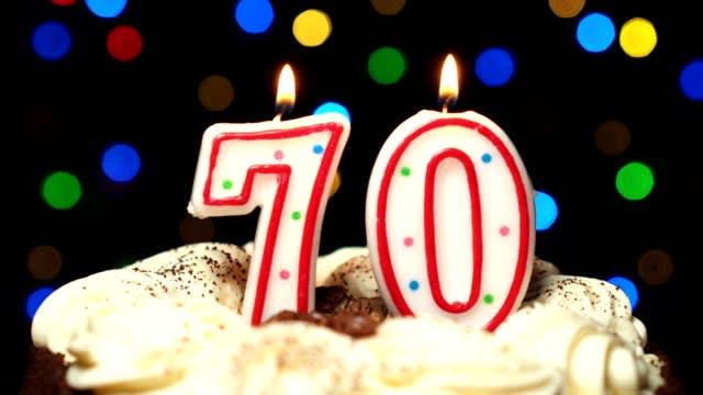 Numéro 70 sur gâteau - anniversaire soixante-dix bougies brûlant - souffler à la fin. Couleur d'arrière-plan flou - Vidéo