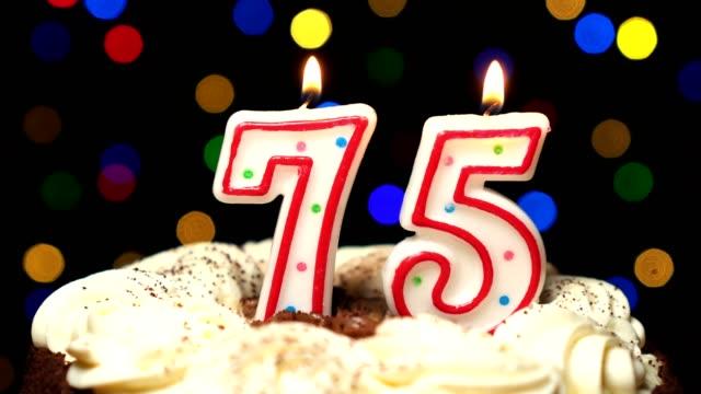 Numéro 75 sur gâteau - anniversaire de soixante-quinze bougie brûle - souffler à la fin. Couleur d'arrière-plan flou - Vidéo