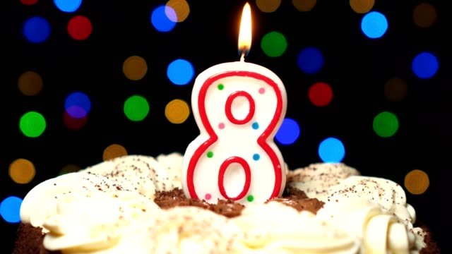 Numéro 8 sur gâteau - anniversaire huit bougies brûlant - souffler à la fin. Couleur d'arrière-plan flou - Vidéo