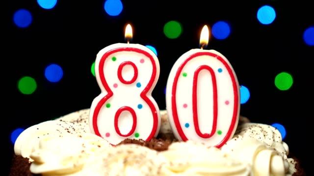 Numéro 80 sur gâteau - anniversaire quatre-vingts bougie brûle - souffler à la fin. Couleur d'arrière-plan flou - Vidéo