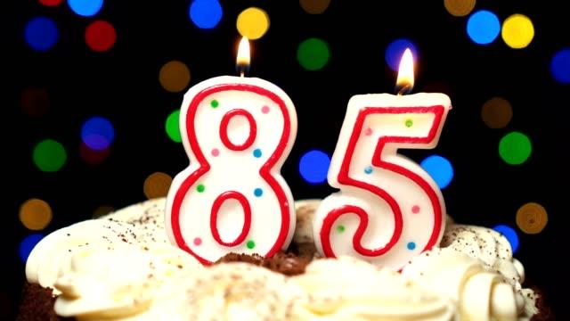 Numéro 85 sur gâteau - anniversaire de quatre-vingt-cinq bougie brûle - souffler à la fin. Couleur d'arrière-plan flou - Vidéo