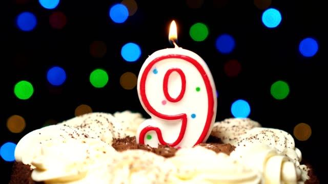 Numéro 9 sur gâteau - anniversaire neuf bougie brûle - souffler à la fin. Couleur d'arrière-plan flou - Vidéo