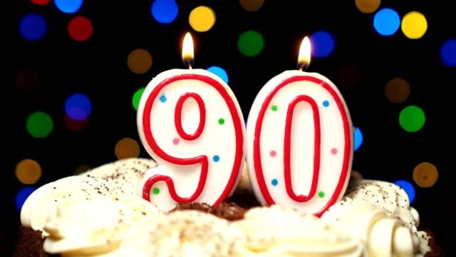 Numéro 90 sur gâteau - anniversaire quatre-vingt-dix bougie brûle - souffler à la fin. Couleur d'arrière-plan flou - Vidéo