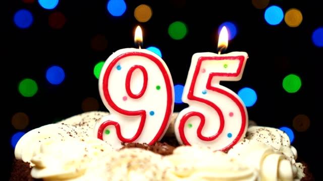 Numéro 95 sur gâteau - anniversaire de quatre-vingt-quinze bougie brûle - souffler à la fin. Couleur d'arrière-plan flou - Vidéo