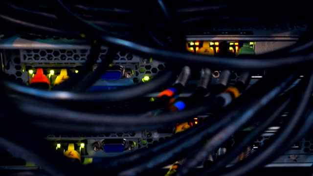 Numerous rows of wires and flashing lights of the server in the data center video