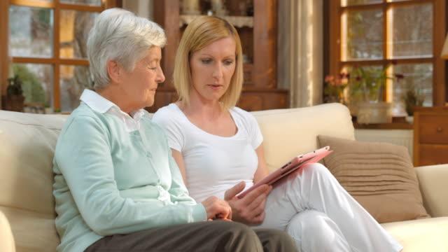 vídeos de stock, filmes e b-roll de ds enfermeira avisar mulher sênior com a ajuda de tablet - assistência à terceira idade