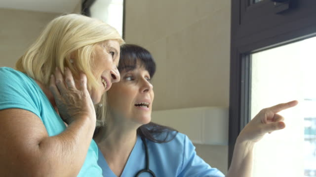 Nurse and patient talking while looking through window video