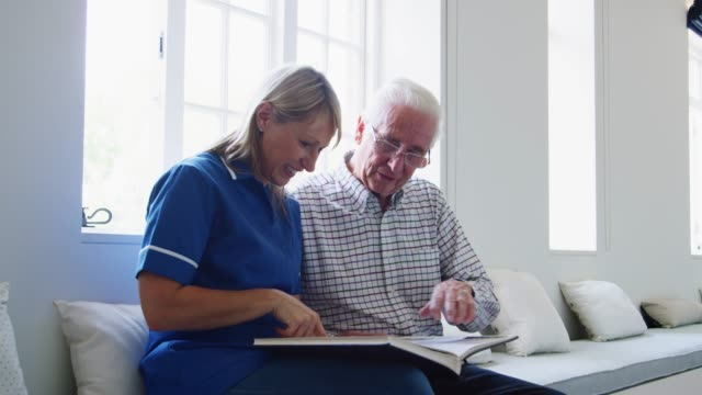 nurse and senior man sitting and looking at a book together - senior care stock videos and b-roll footage