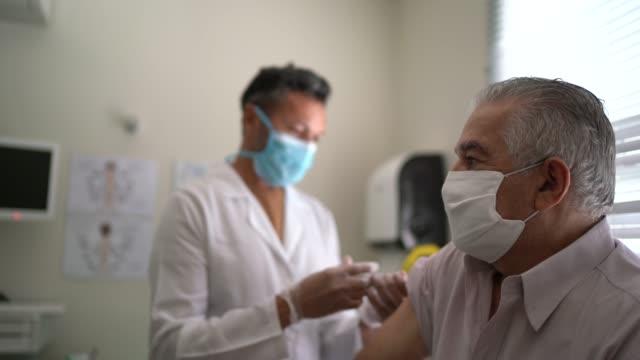 krankenschwester, die impfstoff auf den arm des patienten aufwendet - impfung stock-videos und b-roll-filmmaterial