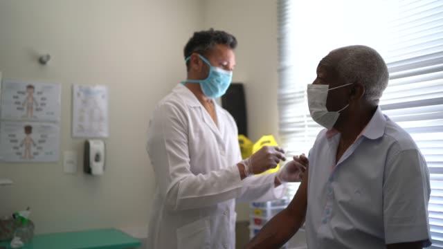 vídeos y material grabado en eventos de stock de enfermera que aplica la vacuna en el brazo del paciente - flu shot