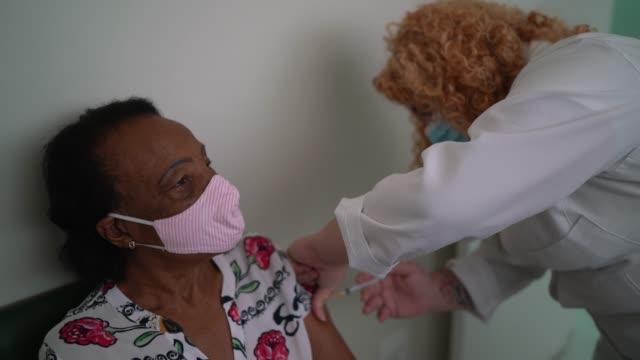 vidéos et rushes de infirmière appliquant le vaccin sur le bras du patient - vaccin covid