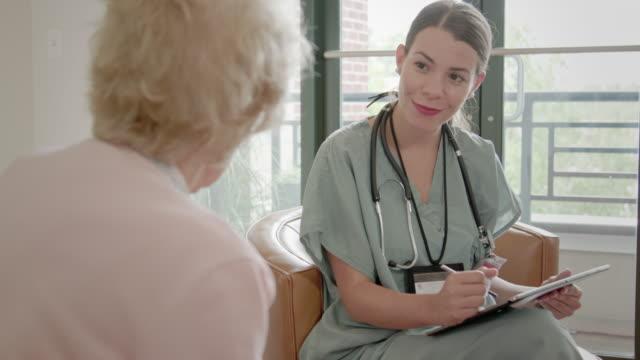 üst düzey kadın bir dijital tablert kullanarak sorular sorar hemşire - ziyaret stok videoları ve detay görüntü çekimi