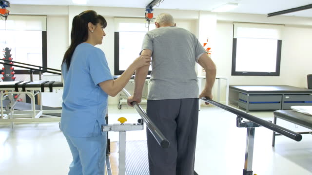 nurse assisting senior man in walking between bars - fisioterapia video stock e b–roll